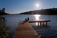 A couple awaits sunset on a dock at Duncan Bay at Isle Royale National Park in Michigan USA.