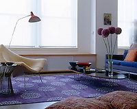 The vase of alliums arranged on the coffee table in the living room of a New York apartment complement the contemporary carpet covered in large silver flower mofifs