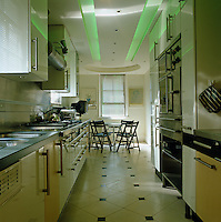 A table and chairs at one end of this galley kitchen is illuminated by modern green recessed lighting