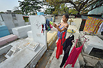 """In the capital of the Philippines, Aramay Calma hangs laundry over tombs in the Manila North Cemetery, where she lives. Hundreds of poor families live here, dwelling in and between the tombs and mausoleums of the city's wealthy. They are often discriminated against, and many of their children don't go to school because they're too hungry to study and they're often called """"vampires"""" by their classmates. With support from United Methodist Women, KKFI provides classroom education and meals to kids from the cemetery at a nearby United Methodist Church."""