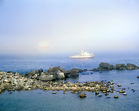 Fishing boat and Coquille River Lighthouse in early morning fog at Bandon, Oregon