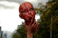 D.F. Mexico, November 23. 2013.  A man holds the head of a toy while Thousands of people dressed as zombies take part in a march from the plaza of the three cultures on the Paseo de la Reforma Avenue to the Angel of Independence.  VIEWpress/Miguel Angel Pantaleon