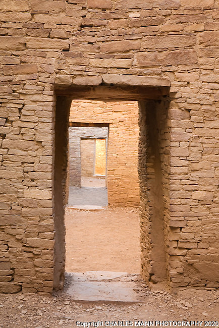 Light filters down between interior doors of layered stone inside Pueblo Bonito and Chaco Culture National Historical Park.