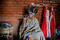 Witchdoctor Arnaldo Rodis, (45), drinks a Coke during a spiritual ceremony.