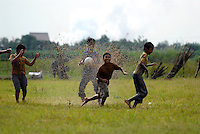 Boys playing football in the mud near the destroyed village of Kedung Bendoh. Since May 2006, more than 10,000 people in the Porong subdistrict of Sidoarjo have been displaced by hot mud flowing from a natural gas well that was being drilled by the oil company Lapindo Brantas. The torrent of mud - up to 125,000 cubic metres per day - continued to flow three years later.