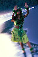Local Hawaiian young woman dancing in Waipio Valley wearing ti leaves skirt maile lea
