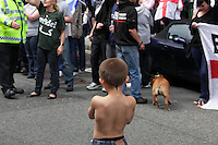 Young boy looking isolated from mother during EDL demonstration in London, UK, 31/7/10