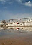 Snow fence and a fire hydrant reflect in a puddle at Nauset Beach in Orleans.