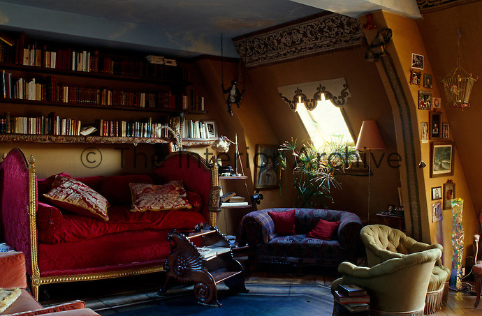 A magnificent Louis XV daybed has been placed beneath a bookcase painted in 'faux bois'