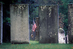 Lone American Flag seen between two grave stones.