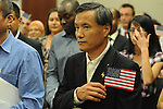 Shengkun Wen holds a flag after becoming United States citizens during a naturalization ceremony in federal court in Oxford, Miss. on Friday, June 29, 2012. Forty seven persons took the oath of citizenship.