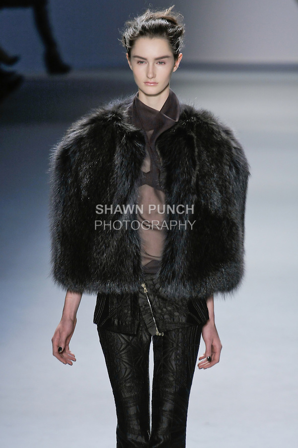 Mackenzie Drazan walks runway in a charcoal Raccoon cape, brown sleeveless silk chiffon cowl neck top over dark green vault jacquard strapless bra, and dark green vault jacquard flared pant with zip-front peplum, from the Vera Wang Fall 2012 Vis-a-gris collection, during Mercedes-Benz Fashion Week Fall 2012 in New York.