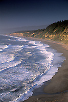 Waves crashing on curved sand Agate beach at sunset below cliffs at Patricks Point State Park, near Trinidad, Humboldt County, California.