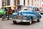 Havana, Cuba; a classic blue 1947 Oldsmobile car driving down the street in Old Havana