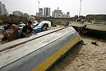 Palestinian fishermen fix their boats in the port of Gaza City on March 31, 2013. An Israeli military spokesman announced on March 21, that the Israeli military will again reduce the permitted fishing range in the Gaza Strip from six nautical miles to three (approximately 5.5 kilometres), in response to missile fire by armed Palestinian groups towards the south of Israel earlier that morning. Photo by Emad Nassar