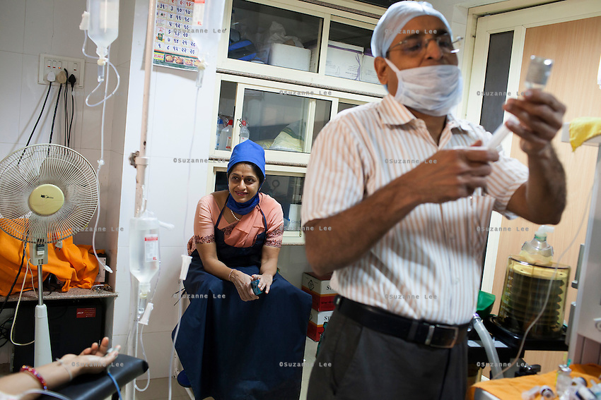 Dr. Nayana Patel (center) waits for the next operation after performing a hystroscopy, a pin-hole operation, on a patient in the operation theater of Akanksha IVF and Surrogacy Clinic in Anand, Gujarat, India on 11th December 2012. Photo by Suzanne Lee / Marie-Claire France