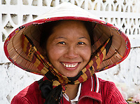 The silk chin strap for the straw hat is a frequently seen fashion accessory in Laos.<br /> (Photo by Matt Considine - Images of Asia Collection)