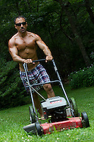 man at home in the yard mowing the lawn