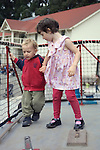 Sausalito CA Girl, four-years-old helping guide brother, two, in Bay Area Discovery Museum play yard  MR