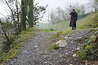A man in an overcoat trying to make a call when there's limited mobile reception by standing in a raised clearing, in woodland near Calstock, Cornwall