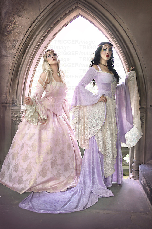 A blond woman and a brunette woman in fancy  pastel renaissance costumes in front of an archway