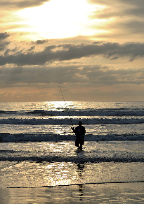Fisherman on the Beach at Cocoa Beach, Florida at Sunrise
