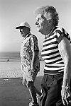 Two sun tanned old age pensioners power walking Bondi beach Sydney Australia.