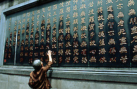 China. Province of Zhejiang. Hangzhou. Lingyin Si Temple. Temple of the Soul's Retreat. Buddhism. An old woman with gray hair lays her hand on the depositaries of buddhist texts. Chinese writing.  © 2004 Didier Ruef