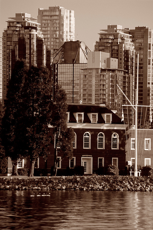 Colonial style building with office towers and condominiums in background, Coal Harbor, taken from seawall in Stanley Park, Vancouver, BC.