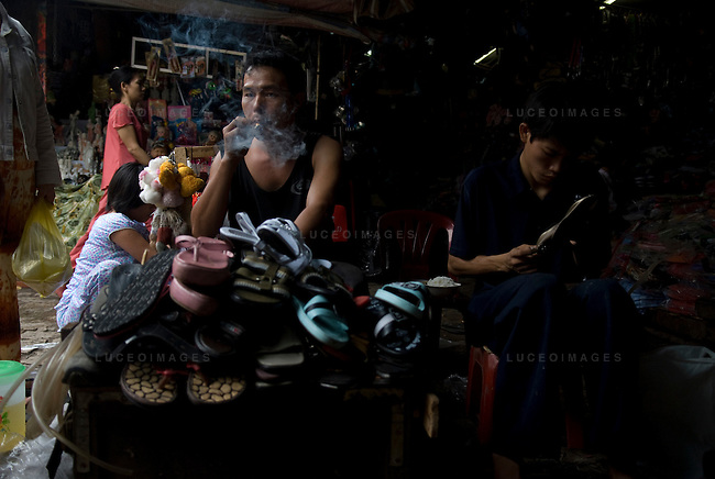 Vietnamese men smoke in the market in Ho Chi Minh City, Vietnam.