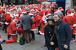 Tourist Lndon Christmas having their photograph taken with a group of Father Christmas's