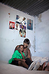 Khayelitsha, South Africa March 5, 2013: Palesa, a young soccer player with her mom Khulliswa In their small room next to the grounds of Amandla EduFootball program. It was founded by Jakob Schlichtig, Florian Zech outside the field in Khayelitsha a poor township outside Cape Town, South Africa. They use football to initiate, support educational projects for youth in the township. The program keep children busy and it decreases the risk of them joining gang, criminal activity or teenage pregnancy. The crime level has decreased substantially in the area since the program was created in 2006. (Photo by: Per-Anders Pettersson)