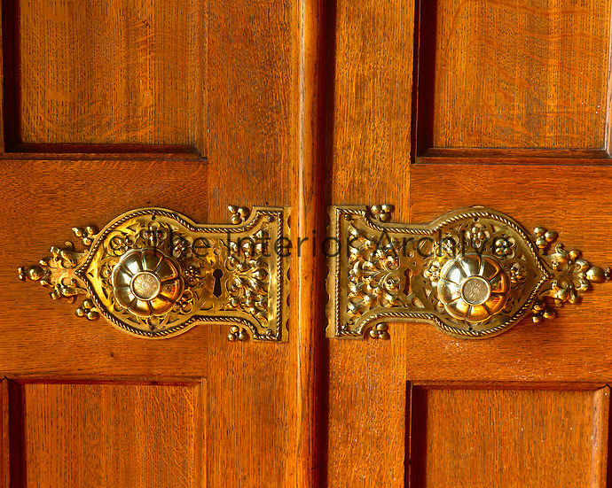 A pair of ornate door knobs decorate a double door