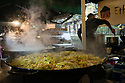 London, UK. 15.11.2014. Curry in a large paella pan, cooking on a stall at Borough Market., with a man stirring another dish in the background. Photograph © Jane Hobson.