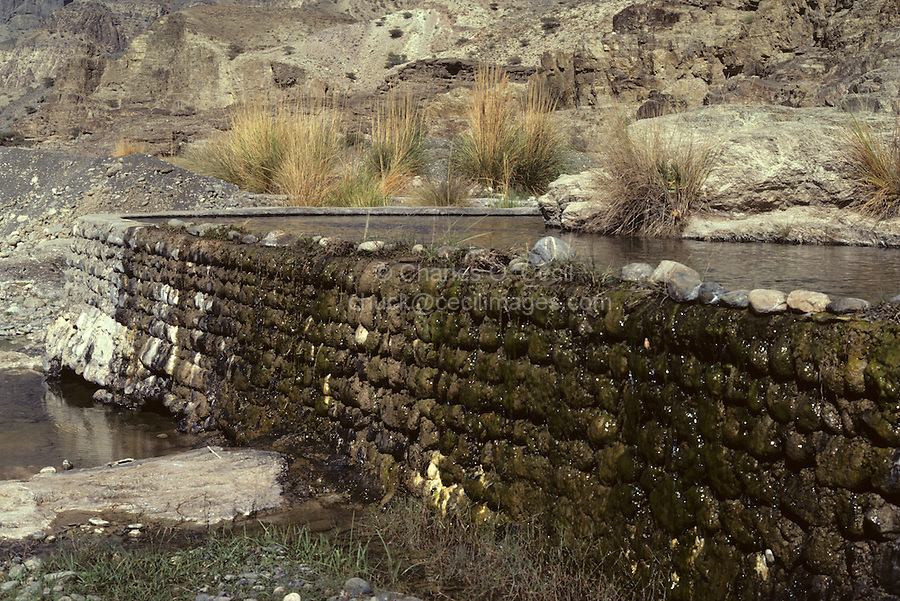 Wadi Daika, Oman, Arabian Peninsula, Middle East - A stone wall creates a reservoir to allow controlled flow of mountain spring water for irrigation. These water systems, known as aflaj (singular, falaj) date back centuries, traceable to Iranian origins.