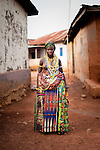 A Dipo-Yo (adolescent girl undergoing Dipo) stands adorned in beautiful beads and cloths on completion of the Dipo puberty rites. The bolts of cloth are gifts from family and friends, and the beads she wears are a form of wealth, handed down from mother to daughter through the generations. Each design has a particular significance. During Dipo, the number of beads worn by a girl is indicative of her family's wealth, as well as the strength of her relationship with them - if she is seen to be respectful older relatives will pitch in and lend her their beads. The beads may weigh as much as 15kg, and are exhausting and often painful to wear.