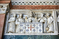 Late medieval relief sculpture depicting St Martin giving his sacred literny on the Facade of the Cattedrale di San Martino,  Duomo of Lucca, Tunscany, Italy,