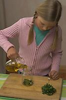 Mädchen macht Heilöl mit Gänseblümchen und Olivenöl, zerkleinerte Gänseblümchen werden in ein Glas gefüllt und mit Öl übergossen, Bellis perennis, Daisy