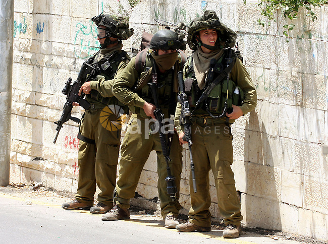 Israeli soldiers stand guards during the clashes in the West  Bank village of Nabi Saleh, on 28 May 2010. Palestinians protest weekly against the neighbouring Jewish settlement of Halamish. photo by Eyad Jadallah