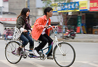 Couple on a tandem bicycle in Yangshuo street, China