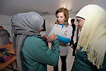 Felomain Nassar-Batshone (center), program manager for the Jordan program of International Orthodox Christian Charities, helps girls put on their new school uniforms during a class session in the Zaatari Refugee Camp, located near Mafraq, Jordan. Opened in July, 2012, the camp holds upwards of 50,000 refugees from the civil war inside Syria. International Orthodox Christian Charities, which provided the uniforms, and other members of the ACT Alliance are active in the camp providing essential items and services.