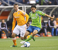 Seattle Sounders FC defender Leonardo Gonzalez  keeps teh ball away from Houston Dynamo forward Will Bruin during play at Qwest Field in Seattle Friday March 25, 2011. The match ended in a 1-1 draw.