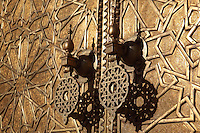 Golden handles on the doors of the Royal Palace, 17th century, Fes, Fes-Boulemane, Northern Morocco. The Royal Palace compound in Fes-el-Jedid covers 80 hectares and contains gardens, mosques and a 14th century madrasa or religious school. As a residence of the king of Morocco it is closed to the public. Fes-el-Jedid was founded in 1244 as a new capital by the Marinid dynasty, and contains the Mellah, or Jewish quarter. Picture by Manuel Cohen