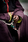 "A local villager is seen with prayer beads while waiting for His Holiness the Twelfth Gyalwang Drukpa, the head of the Drukpa Lineage to arrive in the outskirts of Hemis in Shwang. ""Walking On The World's Rooftop"" Pad Yatra from Manali to Ladakh, of 400kms was focused at raising awareness awareness of His Holiness' charitable projects including education , environment and cultural preservation of tribal people from the area. Accompanied on the Yatra by large numbers of Buddhist monks, nuns, foreigners and local villagers. The culmination of the Pad Yatra coincides with the colourful age-old Hemis festival in Leh, Ladakh, India."
