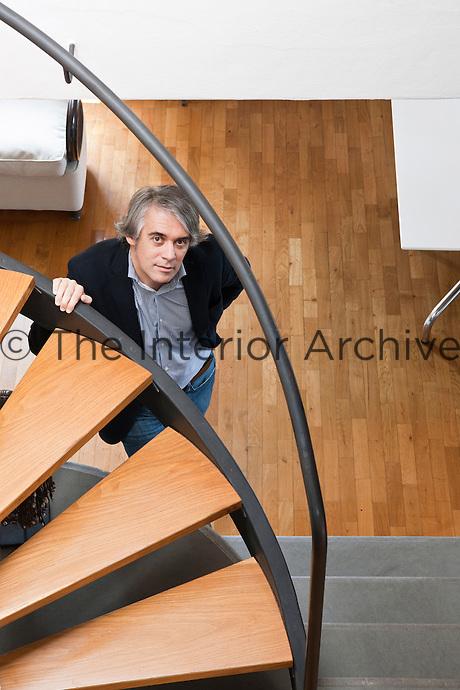 Fabio Sartoretto looking up through his spiral staircase