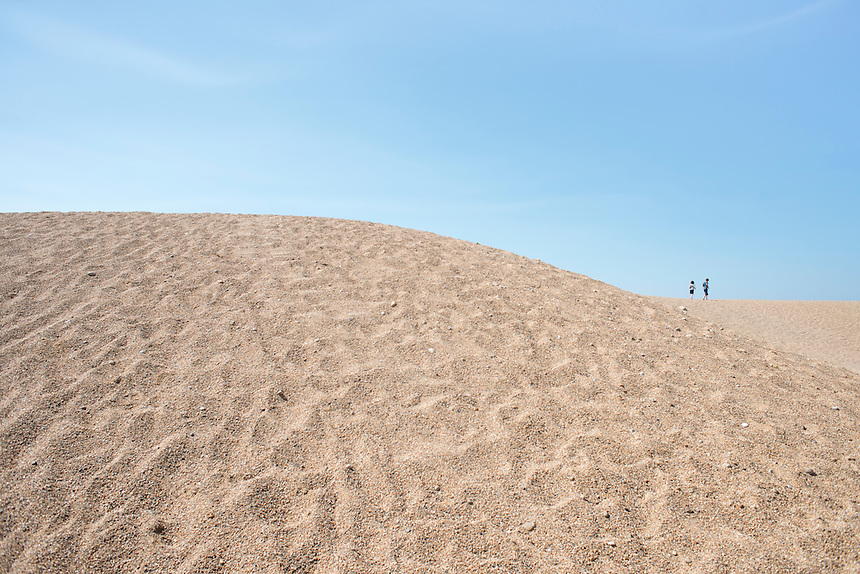 Felix and Lucas on a sand dune. Summer day at West Bay, Brid Port, Dorset, UK.
