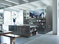 The modern, industrial stainless steel kitchen, by Antonio Citterio for Arclinea, is built to display artwork as well as kitchenware. The photograph is by Armin Linke