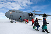 Passengers from a plane stepping onto the ice of McMurdo Sound, Antarctica.