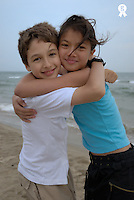 Two children (12-13) embracing on beach, smiling, portrait, close-up (Licence this image exclusively with Getty: http://www.gettyimages.com/detail/200482301-001 )