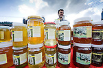 Selling local honey at the large Sunday market in Zarnesti, near Piatra Craiului national park, Transylvania, Romania